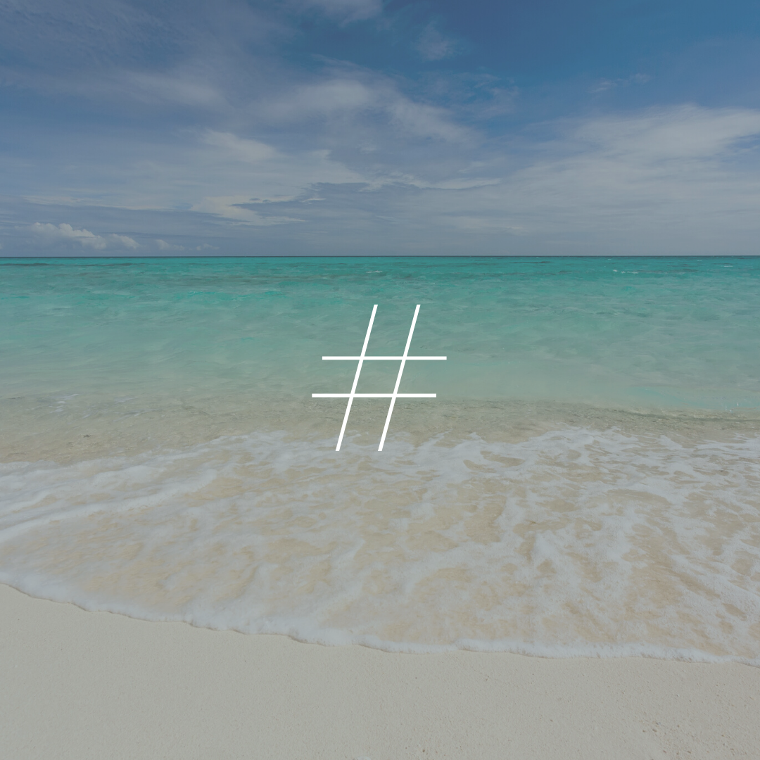 The bright greenish blue ocean laps the shore of the beach behind a white hashtag symbol.