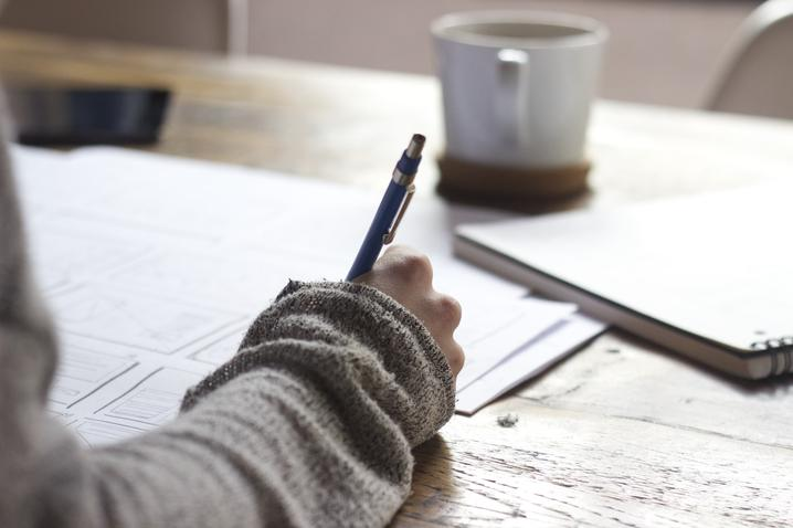 A person holds a pen in their hand like they are writing with a coffee mug in the background.